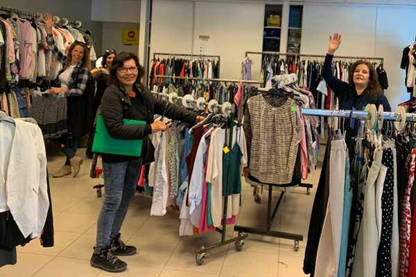 Des bénévoles s'activent autour de portiques de vêtements collectés dans le cadre de l'Entraide proposée aux plus démunis